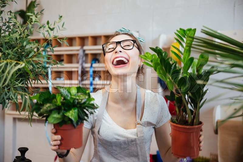 Happy pretty young woman florist holding plants in flowerpots and laughing , stock photo