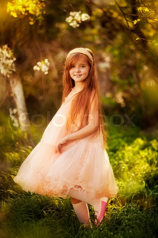 Little Girl With Long Red Hair Dancing In The Spring Garden Stock