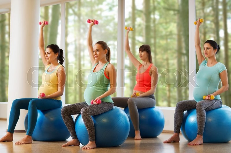Pregnancy, sport, fitness, people and healthy lifestyle concept - group of happy pregnant women with dumbbells exercising on ball in gym, stock photo