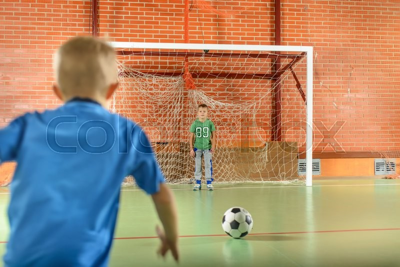 Two young boys playing soccer on an indoor court with one standing in the goalposts as the second prepares to kick for goal, stock photo