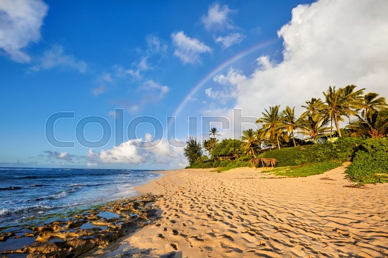 Rainbow scenic view over the popular surfing place Sunset Beach, North Shore, Oahu, Hawaii, USA, stock photo