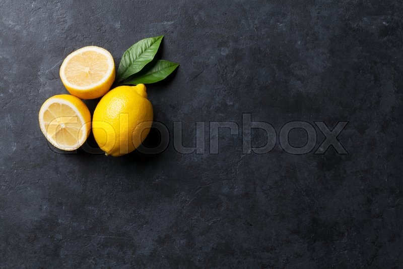 Fresh ripe lemons on dark stone background. Top view with copy space, stock photo