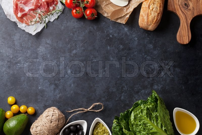 Ciabatta sandwich cooking with romaine salad, prosciutto and mozzarella cheese over stone background. Top view with copy space, stock photo