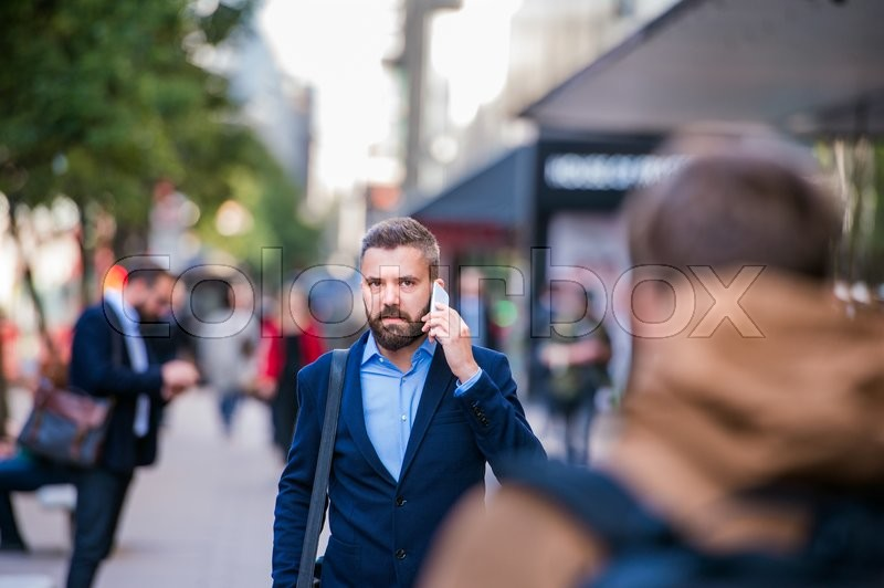 Hipster manager holding a smart phone, making a phone call, walking in the street of London, stock photo