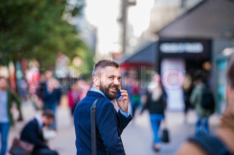 Hipster manager holding a smart phone, making a phone call, walking in the street of London, rear view, stock photo