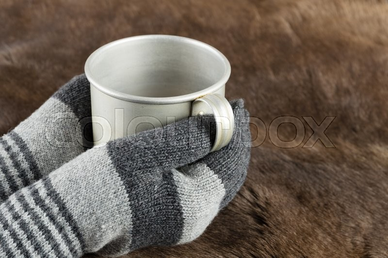 Hands in knitted gloves keep aluminum mug, stock photo