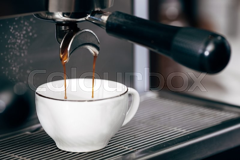 Close-up of espresso pouring from coffee machine, professional coffee brewing, stock photo