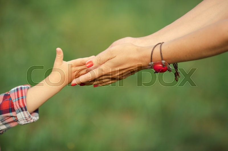 A child hand give his parent something on the nature, stock photo