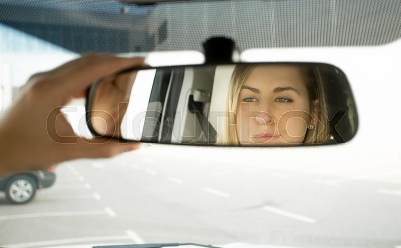 Closeup photo of woman adjusting car mirror and looking in the reflection, stock photo