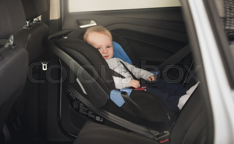 6 months old baby boy sitting in child car seat | Stock Photo ...