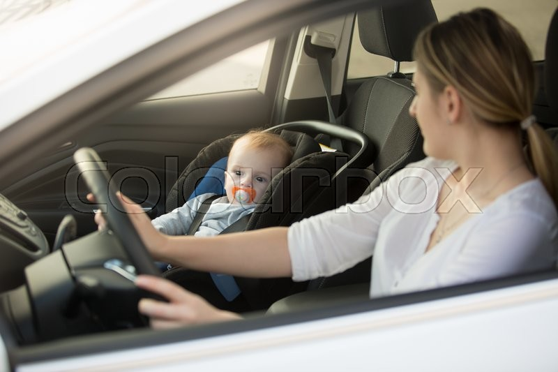 Portrait of woman driving car with baby sitting on front seat ...