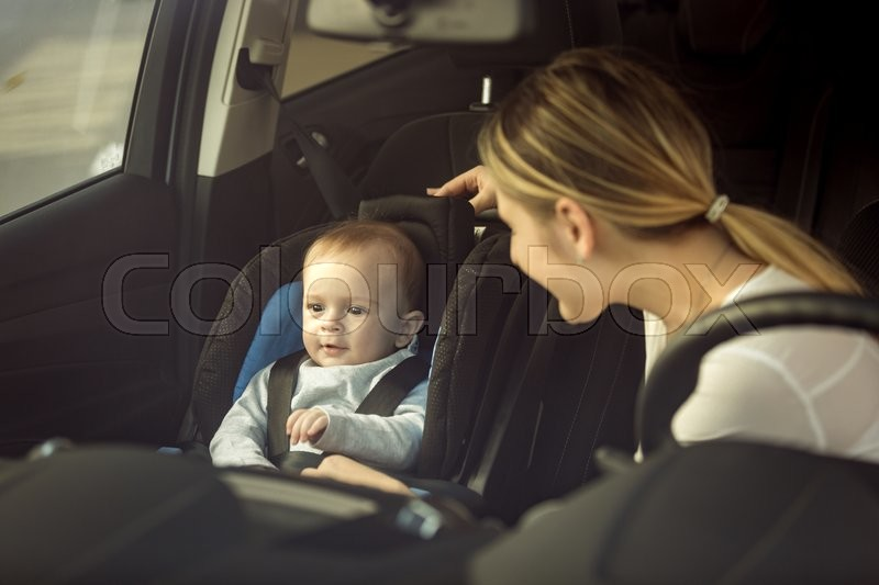 Toned portrait of mother and baby boy sitting in car on front seats, stock photo