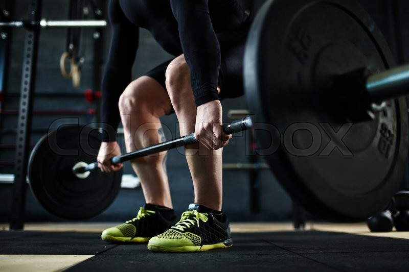 Active young man training with barbell in gym, stock photo