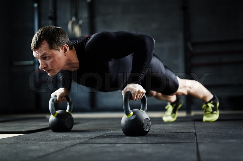 Active young man doing push-ups in gym, stock photo