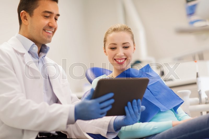 People, medicine, stomatology and health care concept - happy male dentist showing tablet pc computer to woman patient at dental clinic office, stock photo
