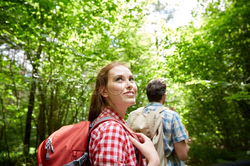 Adventure, travel, tourism, hike and people concept - group of smiling friends walking with backpacks in woods, stock photo