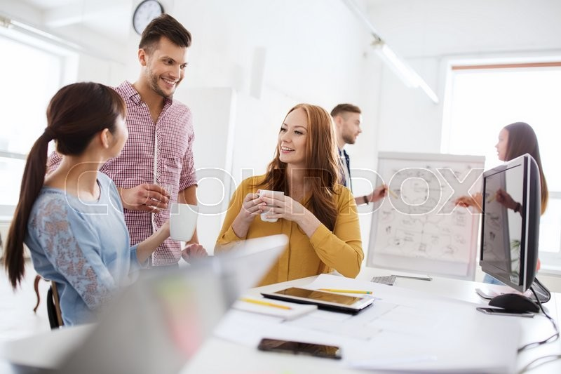 Business, startup and people concept - happy creative team or students drinking coffee at office, stock photo