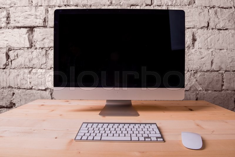 Wooden desk with computer, keyboard and mouse. White brick wall.Copy space , stock photo