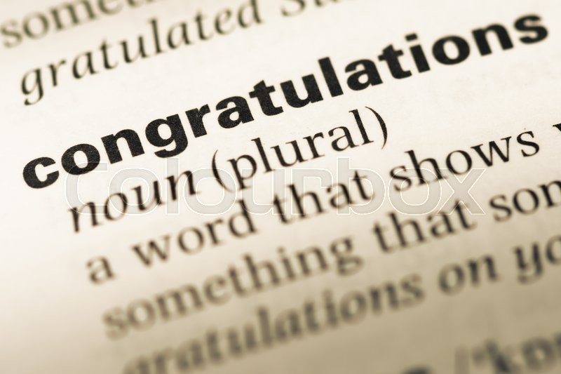 close up of old english dictionary page with word congratulations