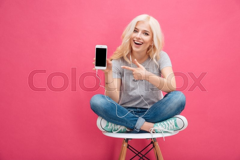 Cheerful woman sitting on the chair and showing blank smartphone screen over pink background, stock photo