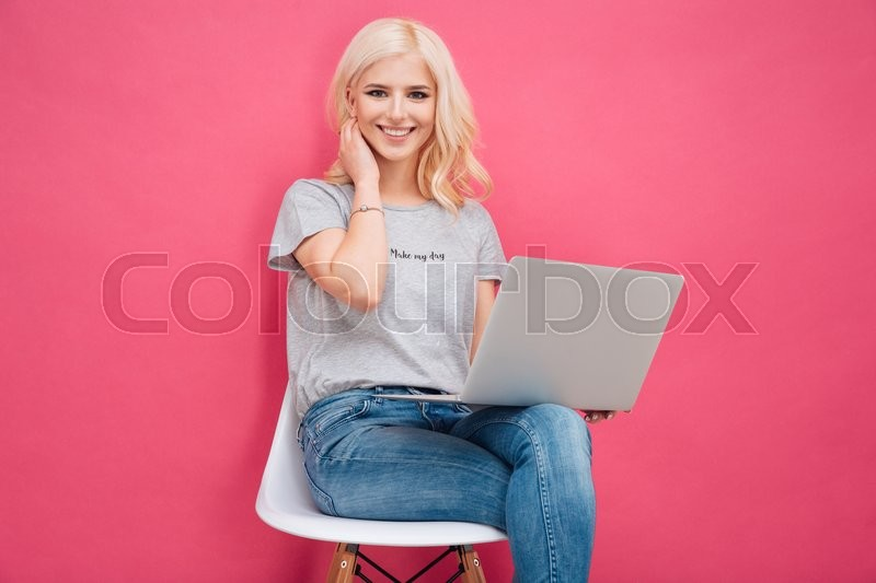 Attractive young woman sitting on the chair with laptop computer on pink background, stock photo