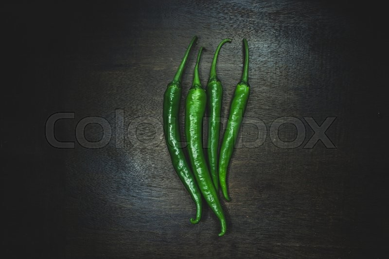 Close up hot peppers spices on black wooden table, stock photo