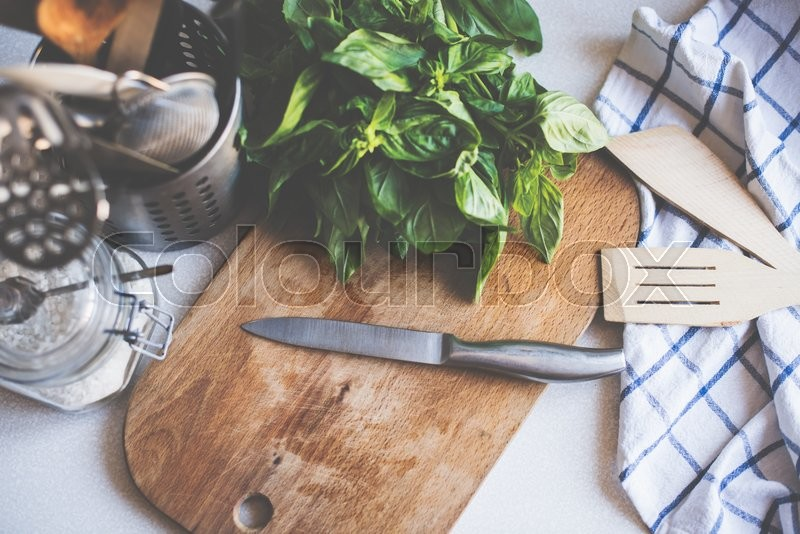 A bunch of basil on the board on the kitchen table, home cooking utensils for cooking, top view, stock photo