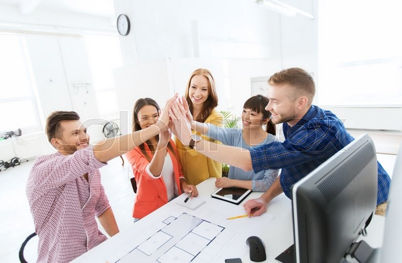 Business, startup, architecture, gesture and people concept - happy international creative architect team or students with blueprint making high five at office, stock photo