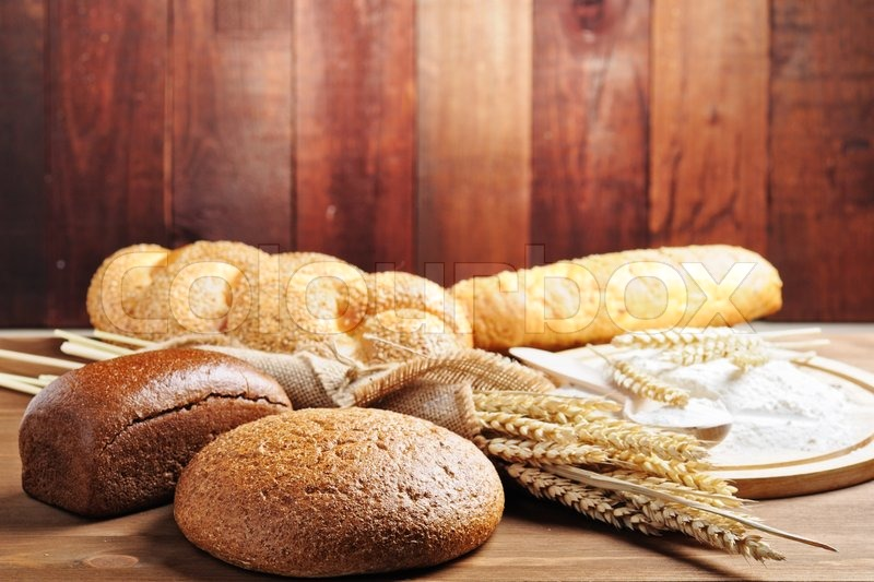 Sliced Bread And Wheat On The Wooden Table Stock Photo