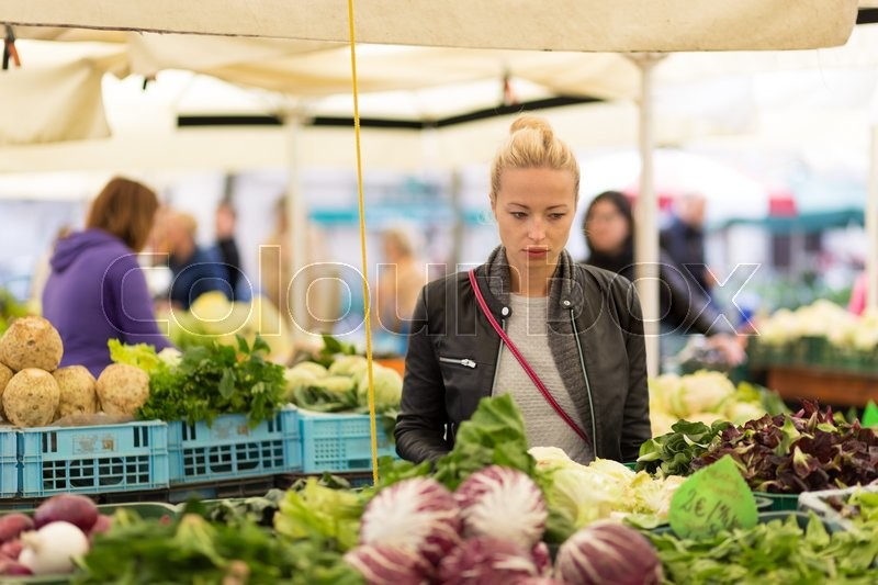 Woman buying fruits and vegetables at local food market. Market stall with variety of organic vegetable, stock photo