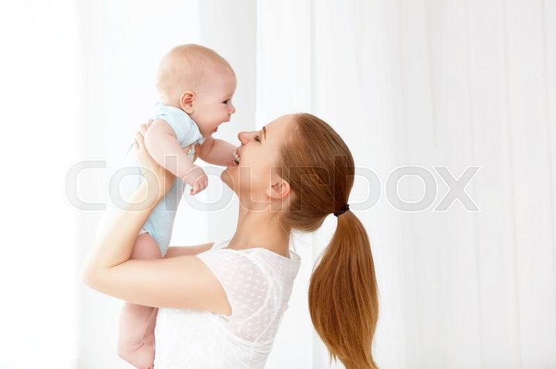 Happy family mother playing with newborn baby, stock photo
