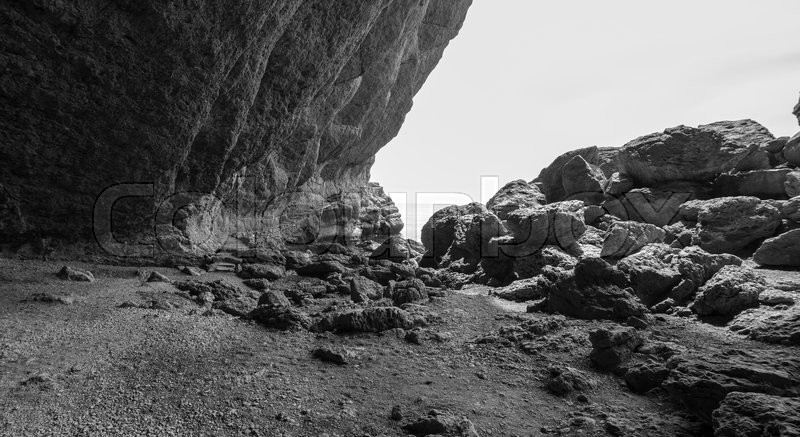 Secluded cove with huge coastal rocks, black and white photo, stock photo