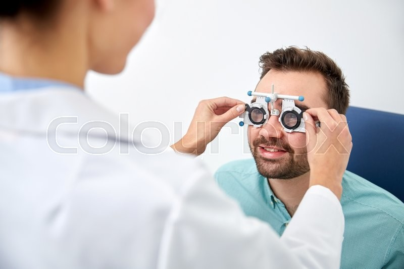 Health care, medicine, people, eyesight and technology concept - optometrist with trial frame checking patient vision at eye clinic or optics store, stock photo