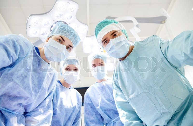 Surgery, medicine and people concept - group of surgeons in operating room at hospital looking into camera, stock photo