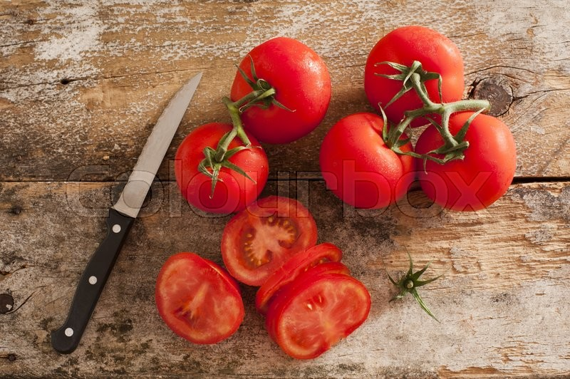 Preparing sliced ripe red tomatoes on a rustic wooden kitchen counter with a paring knife, overhead view of sliced and whole tomatoes on the vine, stock photo