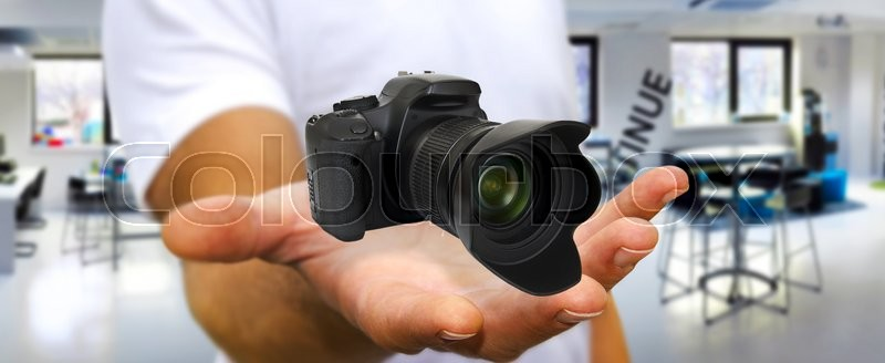 Young man holding modern digital camera in his hand, stock photo