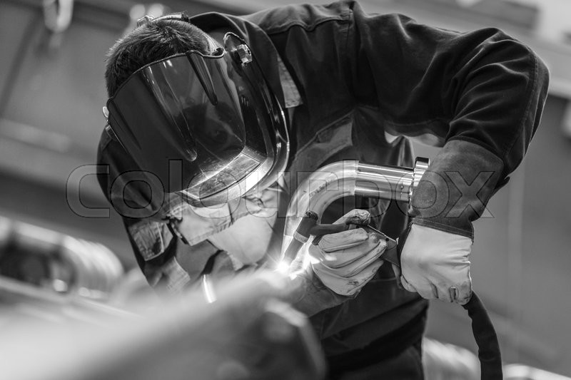 Industrial worker with protective mask welding inox elements in steel structures manufacture workshop. Black and white photo, stock photo