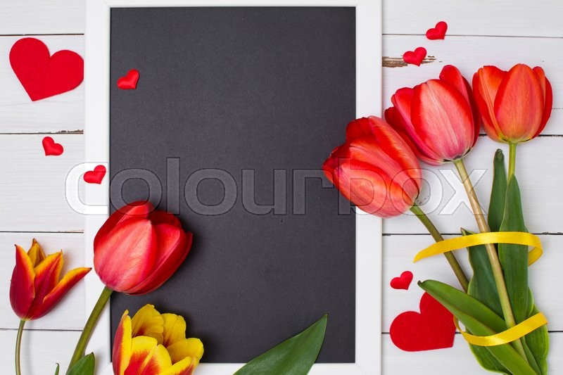 Empty clean black chalkboard with red tulips and hearts. Top view. Valentines day card or template for your design, stock photo