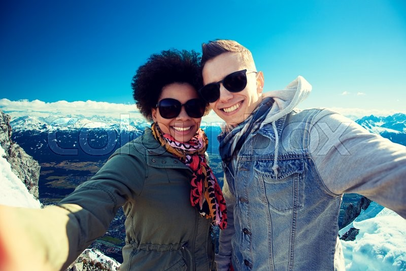 Tourism, travel, people, leisure and technology concept - happy international teenage couple taking selfie over alps mountains in austria background, stock photo