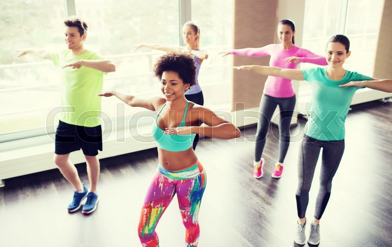 Fitness, sport, dance and lifestyle concept - group of smiling people with coach dancing in gym or studio, stock photo