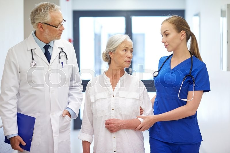 Medicine, age, health care and people concept - male doctor with clipboard, young nurse and senior woman patient talking at hospital corridor, stock photo