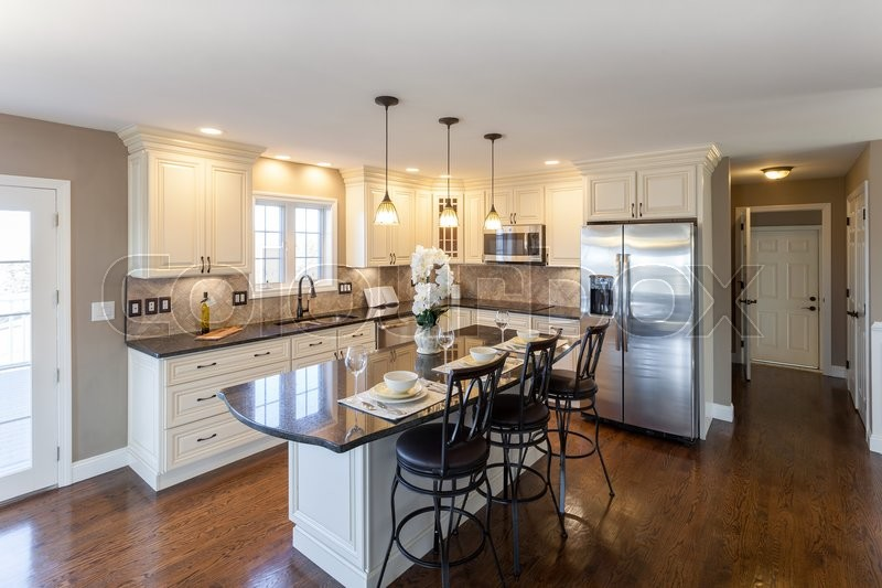 Beautiful staged kitchen room in a modern house with granite countertops and antique finished cabinets, stock photo