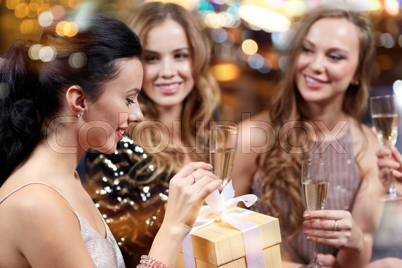 Celebration, friends, bachelorette party, birthday and holidays concept - happy women with champagne glasses and gift box at night club, stock photo