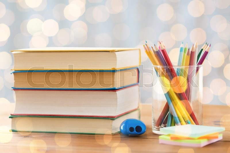 Education, school, creativity and object concept - close up of crayons or color pencils with books, stickers and sharpener on wooden table over holidays lights background, stock photo