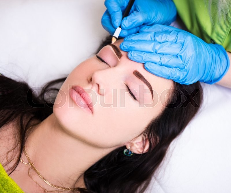 Permanent eyebrow make up - close up of beautician preparing woman for procedure, stock photo