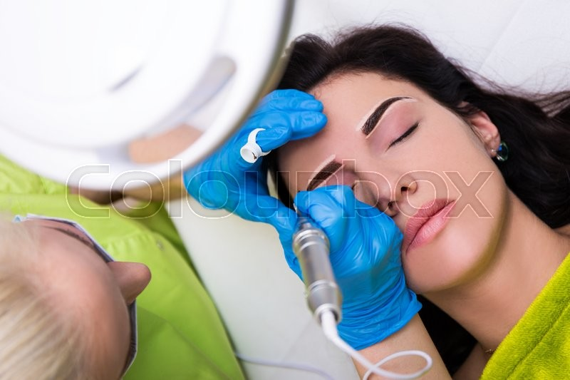 Top view of cosmetologist applying permanent make up on female eyebrows, stock photo