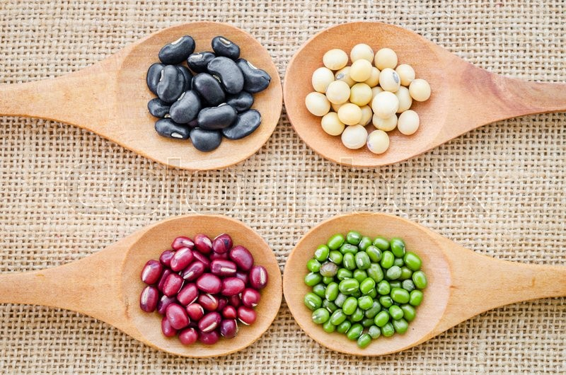 Mix from different beans, black bean, soy bean, azuki bean, mung bean in wooden spoon on the sackcloth background, stock photo