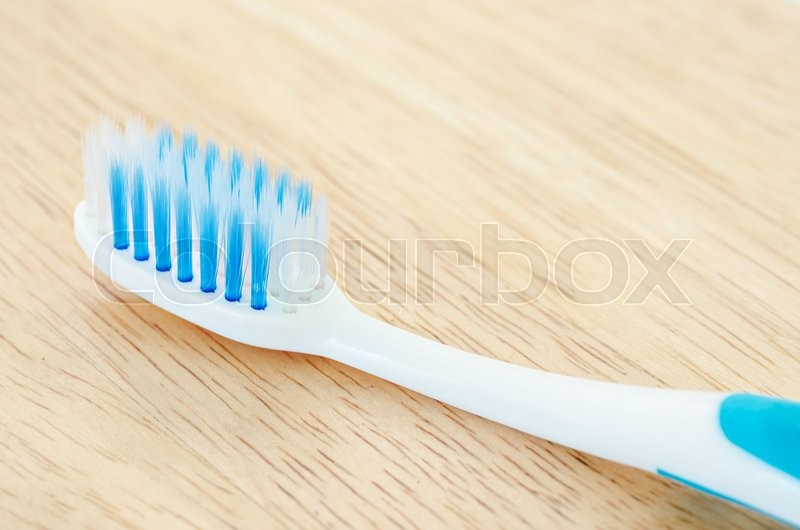 Close up blue color toothbrush on wooden background, stock photo