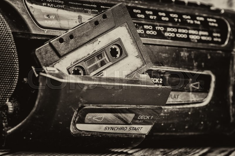Old cassette tape and player on the old brown wooden background, stock photo