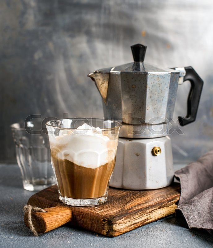 Stock image of 'Glass of coffee with ice cream on rustic wooden board and steel Italian Moka pot. Metal background, selectibe focus'